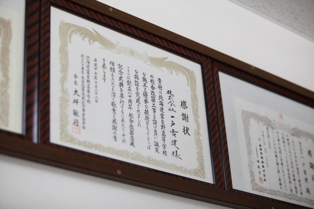 富良野高校の校舎改築工事の際に送られた感謝状。事務所内には地域からの感謝状がずらり。地域貢献は同社の経営理念でもある