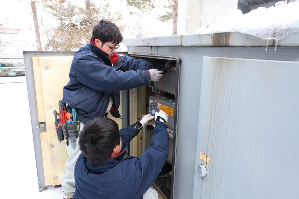 市内山部にある養護老人ホーム「寿光園」の非常用発電機の点検とバッテリーを交換する福田さん、香川さん。年は10歳ほど離れていても同じ高校の先輩・後輩だけあって息はぴったり